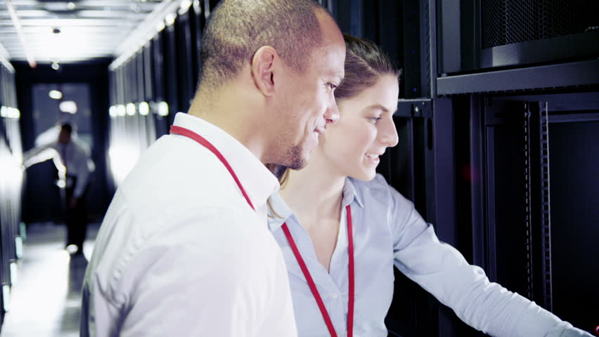 man and woman of mixed ethnicity are working in a data center with rows of server racks and supercomputers. They are checking the equipment and discussing their work.