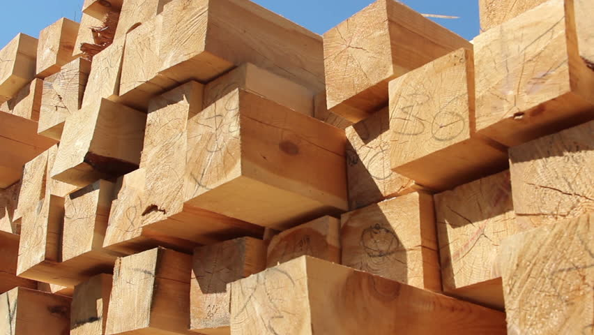 Stack of square wooden chips at construction yard. Dolly pan shot, blue sky