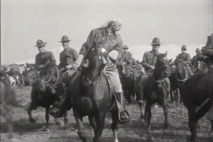 1910s, 1920s - Wild Bill on horseback with his cowboy performers outside a tent.