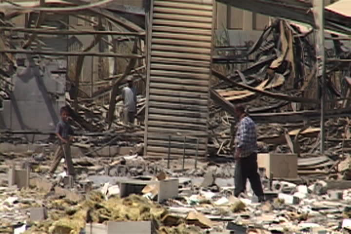 BAGHDAD, IRAQ - JULY 26, 2003: Building rubble, twisted metal and piles of debris. People are walking through wreckage.