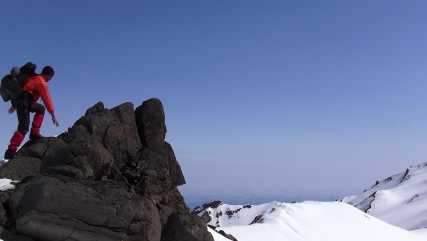 Rock climber on the top of mountain.    Shutterstock HD Video #4084045