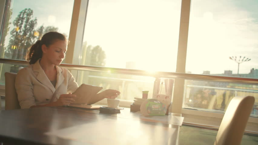 Young beautiful business woman sitting at a table with tablet in hands | Shutterstock HD Video #4087546