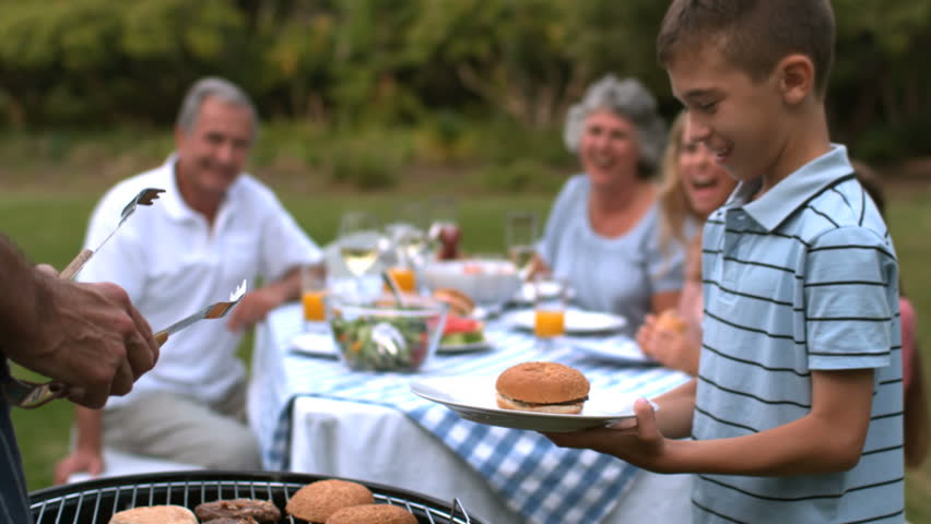Man serving hamburger to little boy in slow motion - HD stock footage clip