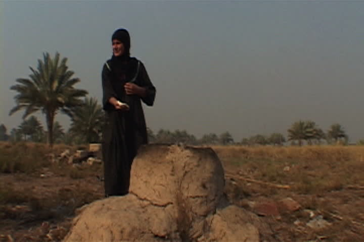 NAJAF, IRAQ - DECEMBER 06, 2003: Woman in black hijab stands in field next to clay oven slapping loaves of bread into shape. - SD stock footage clip