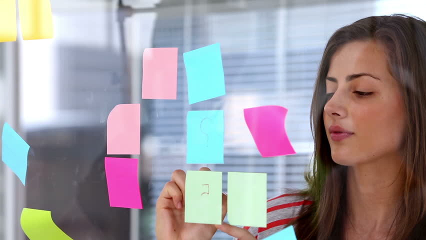 Woman writing on adhesive note with a pen | Shutterstock HD Video #4110874