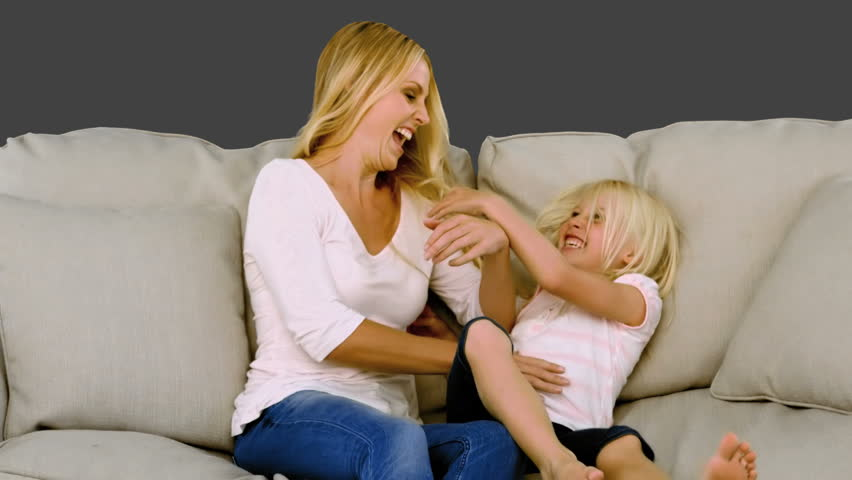 Mother tickling her daughter on sofa in slow motion on grey screen