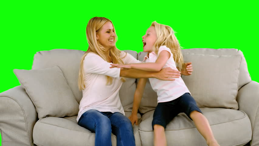 Daughter jumping in the arms of her mother on green screen in slow motion - HD stock video clip