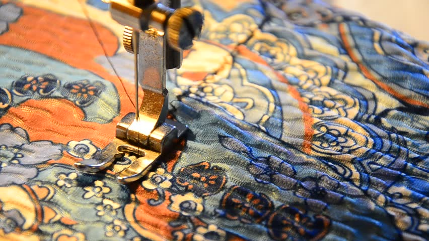sewing machine working part with colorful cloth. Needle stitch zigzag on dramatic light, selective focus
