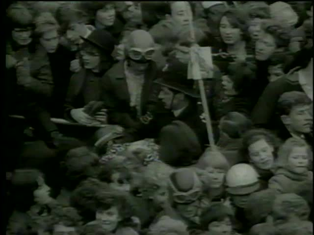 Policemen pick up fainted girl in crowd of the Beatles fans, Heathrow Airport, London circa 1964-MGM PICTURES, UNIVERSAL-INTERNATIONAL NEWSREEL, USA, filmed in 1964