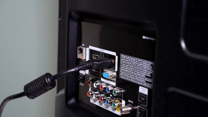 A close-up shot of a workman plugging-in an HDMI cable to the back of a