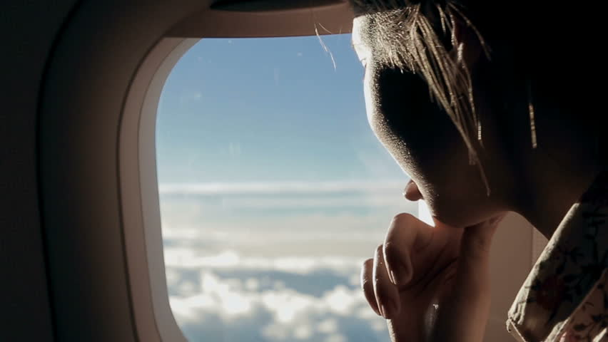 Girl looks at the clouds from airplane window
