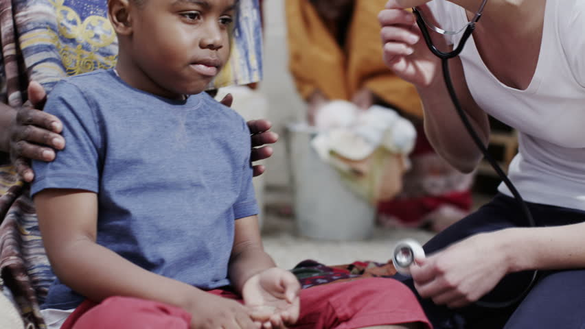 A medical worker from a charity organization chats with the mother of a young boy she has been examining. In slow motion.