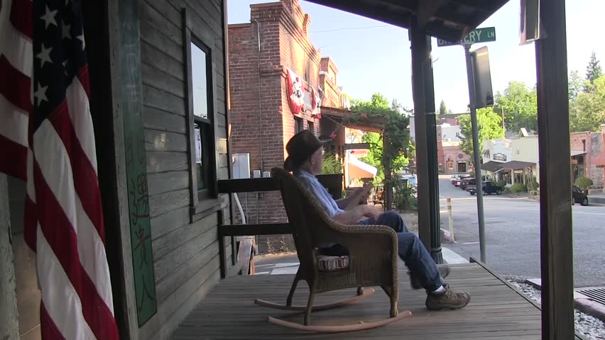 Old small town America man whittling sitting on rocking chair. American flag on sidewalk and old store fronts.