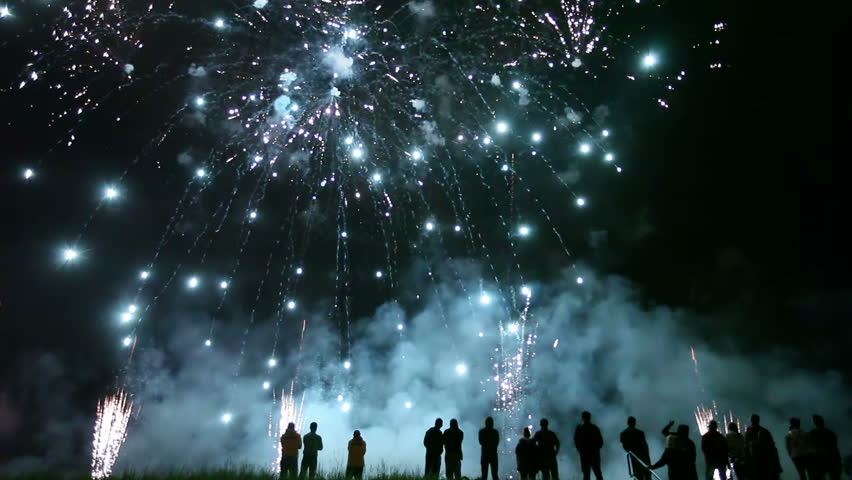 Collage of colorful fireworks exploding in the night sky with sillhouetted people in the foreground watching #4163794