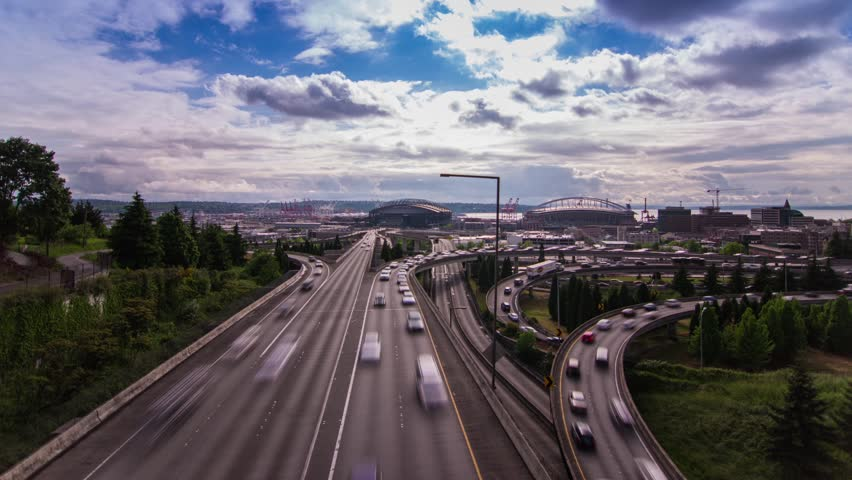 Time Lapse of High Impact Busy Trafic in Seattle. Automobile going back and forth on highway on a Cloudy Afternoon with 2 stadium in the background