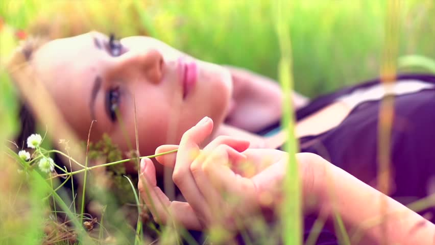 Beautiful Girl Lying on the Meadow and Dreaming. Enjoy Nature. Close up Slow Motion Footage