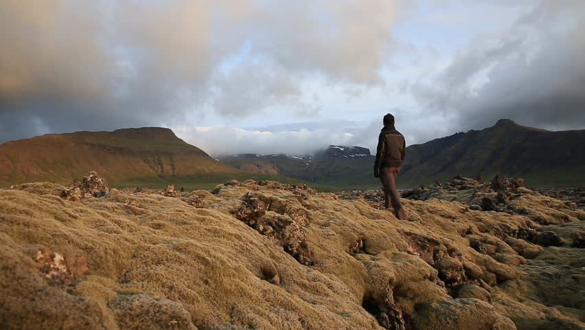 Tourist observing the expansive moss-covered lava fields and mountains in Iceland