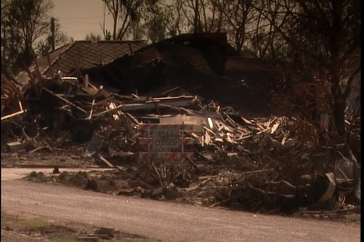 Remains of house and pile of rubble and boards. Camera pans across street to show rubble and overturned cars  in New Orleans after Hurricane Katrina (October 2005).