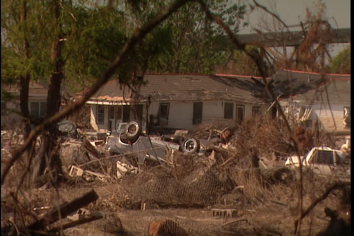 Lot filled with branches, debris and cars. Camera zooms in over debris and overturned truck to crumpled house in New Orleans after Hurricane Katrina (October 2005).