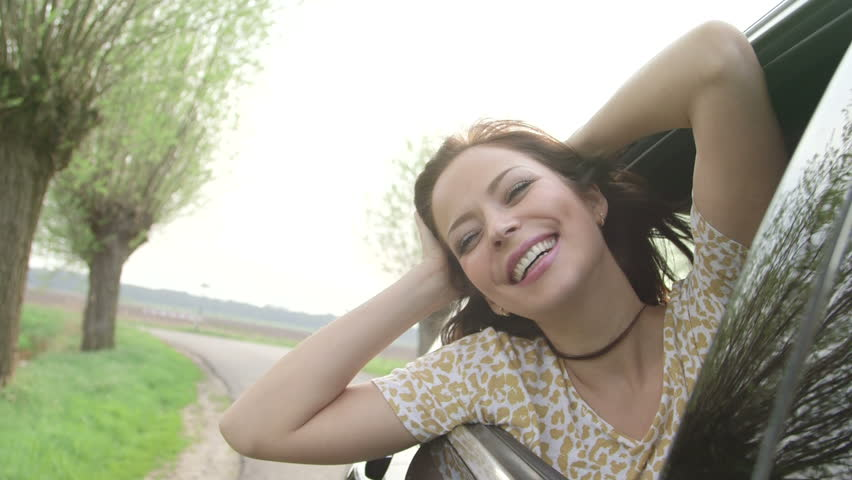 Young woman sitting in car passenger seat looking out window on sunny day with flare  - HD stock footage clip