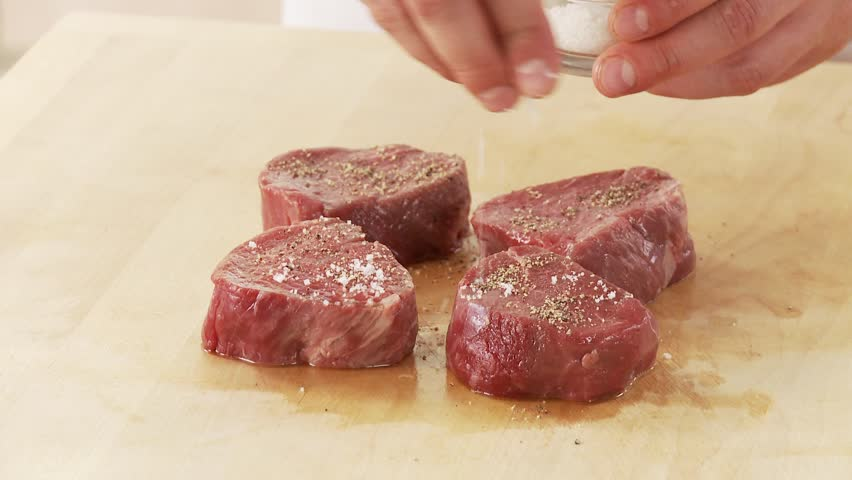 Beef fillet slices being seasoned with pepper and salt - HD stock footage clip