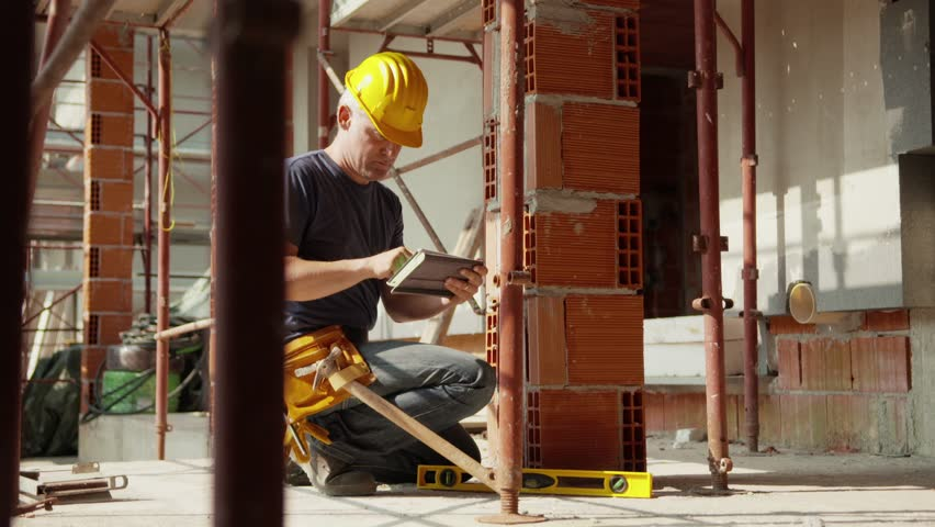 Construction worker and new house, caucasian man working with safety helmet and using digital tablet pc for data entry. Part 7 of 8