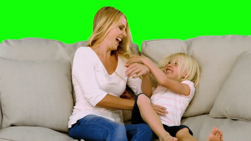 Mother tickling her daughter in slow motion on green screen - HD stock video clip