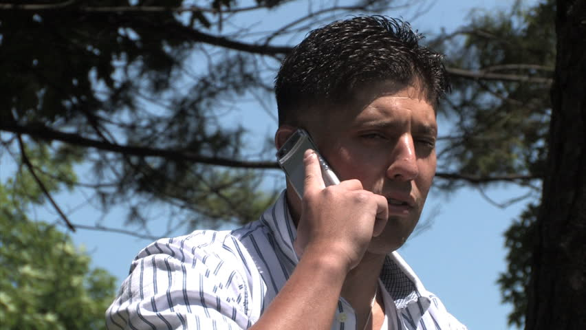 A man talks on a cellular phone in the park. - HD stock video clip