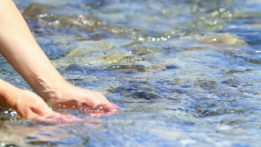 Women hand in transparent water of river.