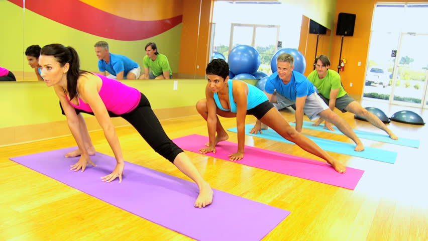 Female fitness instructor putting class through stretching exercises
