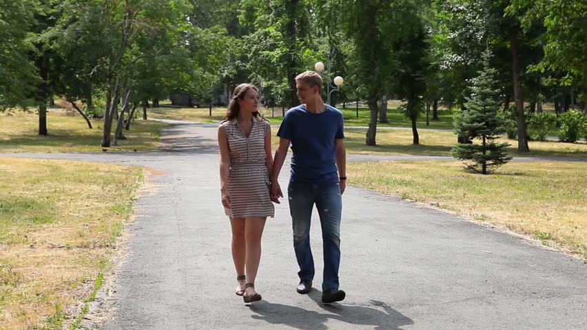 Lovely Young Couple Walking Together In The Park Holding
