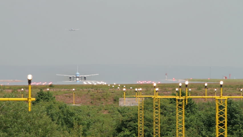 Airplane takes off over landing lights at Manchester Airport, England