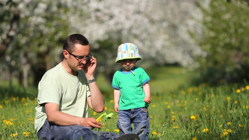 Father and son in orchard with flowers, busy man  talk on the phone, baby leave - HD stock footage clip