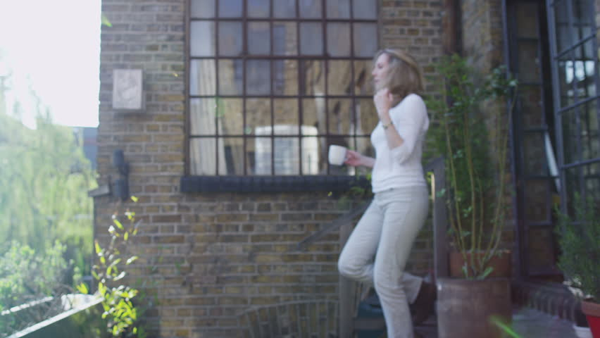 Attractive mature woman enjoying a quiet moment in her garden on a sunny day. In slow motion.