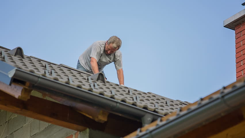 Man Adding New Top Roof Tile. Destroyed roof tiles on completely new house with no facade and no insurance yet. Man changes broken tiles because of hail storm destroyed the roof. - HD stock footage clip