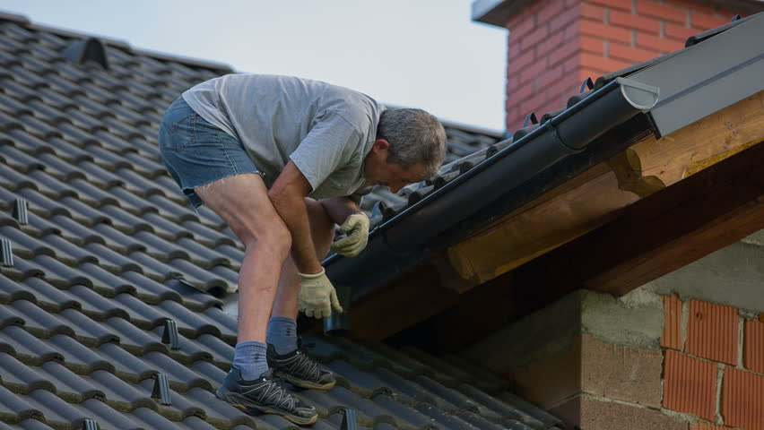 Preparing New Roof Tiles For Changing With Broken Ones. Destroyed roof tiles on new house with no facade and no insurance yet. Man changes broken tiles because of hail storm destroyed the roof. - HD stock footage clip