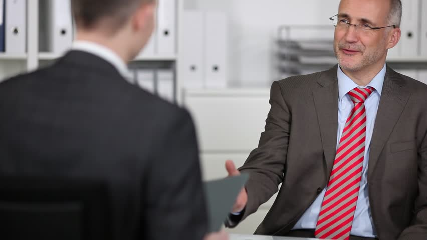 Smiling manager in a job interview accepting a folder containing the curriculum vitae of the applicant, over the shoulder view