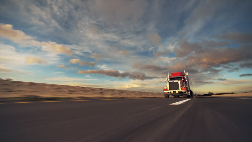 18 Wheel Truck on the road with sunset in the background. Large delivery truck is moving towards setting sun. - HD stock footage clip