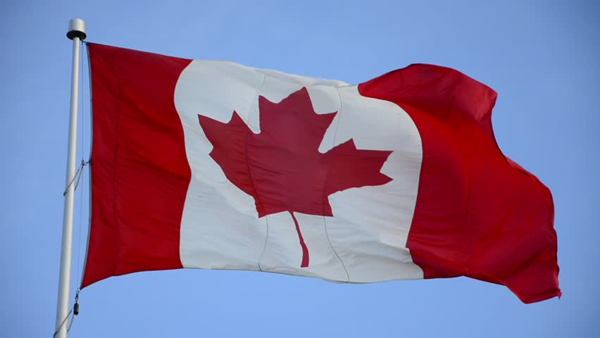 Canadian Flag waving in a windy day. Red and White, the colors of the Canadian Flag