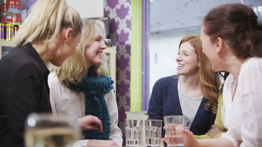 Happy and attractive group of female friends chatting and laughing together in a small cafe or wine bar.