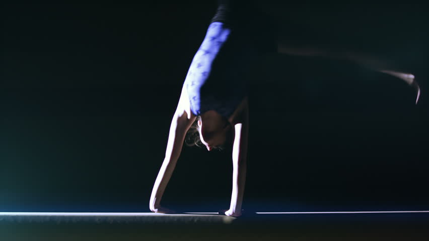 Female gymnast performing on a balance beam in slow motion. Olympics sport in contemporary setting. Slow motion Shot on RED Epic at 240FPS