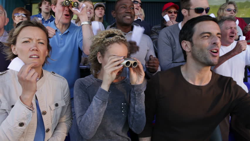 Enthusiastic crowd of spectators at horse racing or dog track.