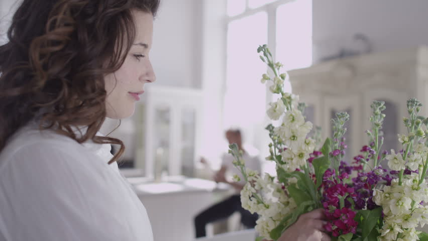Beautiful young woman arranging a vase of fresh flowers and relaxing with her partner in their elegant home.
