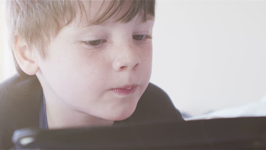 Young boy using touchscreen tablet technology and reading.