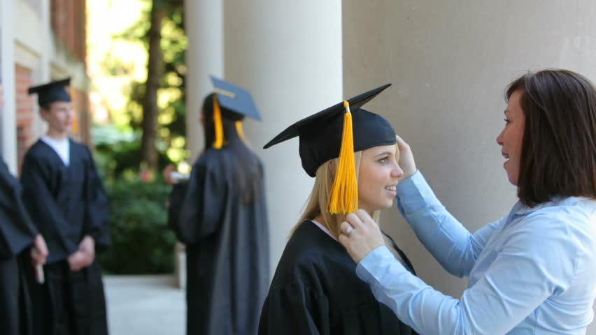 Mother preparing daughter for graduation ceremony