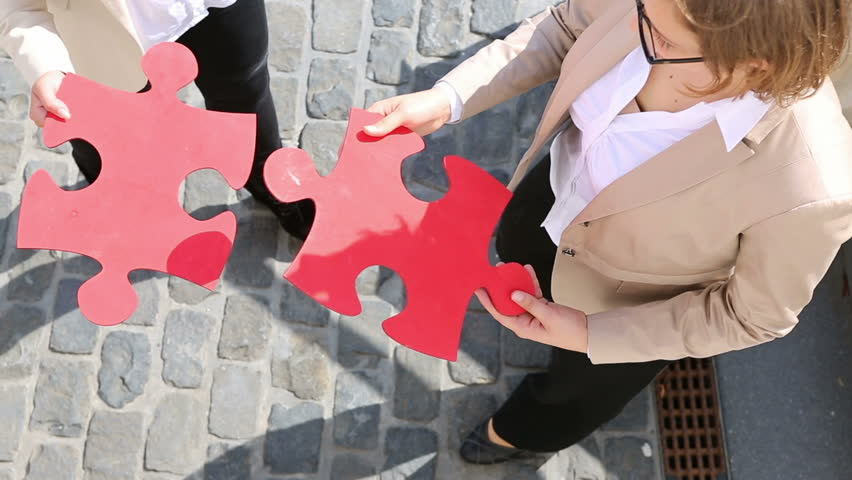 Hands of two business women holding two fitting oversized red jigsaw puzzle pieces