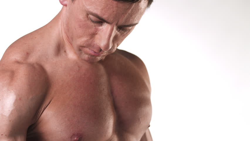 Close up shot of a muscular bodybuilder doing dumbbell curls with his large bicep muscles on a white background, with a camera pan