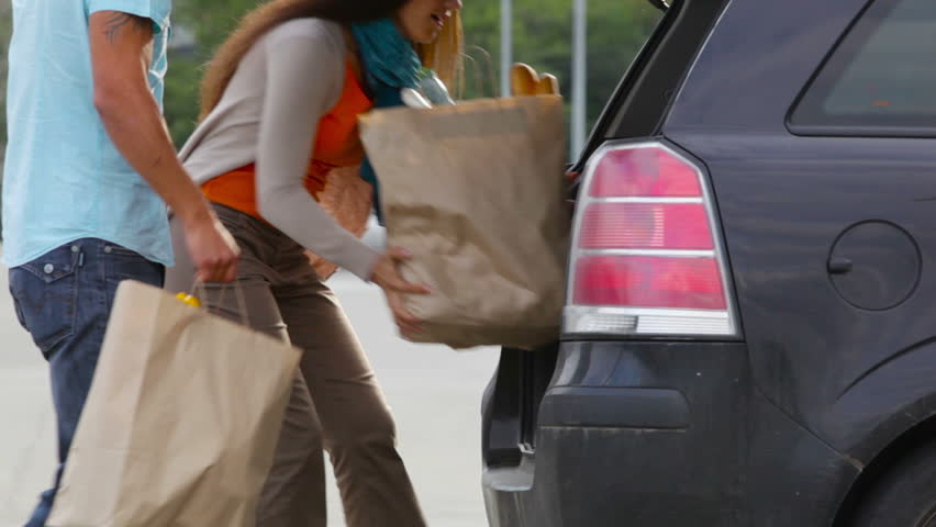 Customers packing groceries in their hatchback
