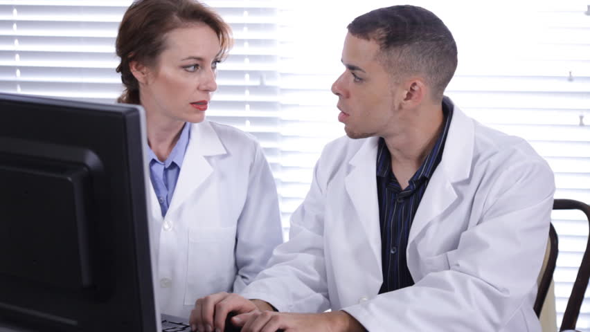 Two doctors, technicians, or scientists working together on a computer. - HD stock video clip