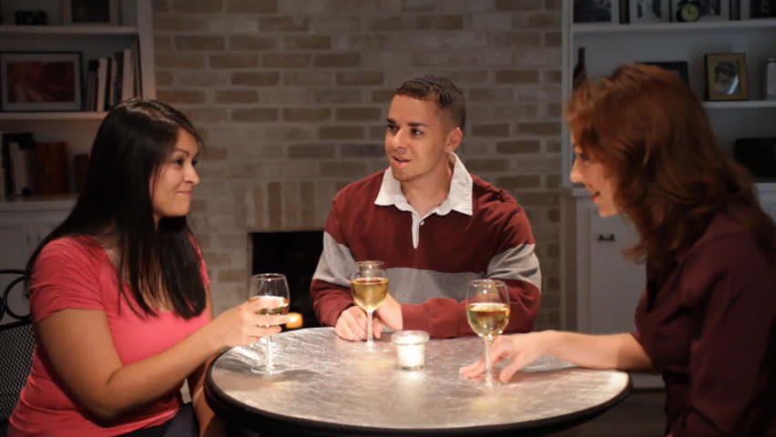 Three friends engaged in conversation raise their wind glasses in a little toast. - HD stock footage clip